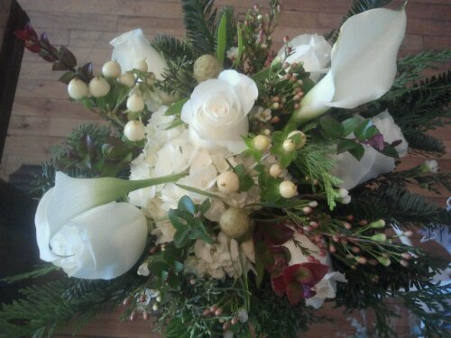 Monochromatic centerpiece with mixed winter greens white callas roses hypericum berry